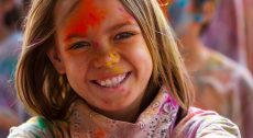 smiling girl covered with colors